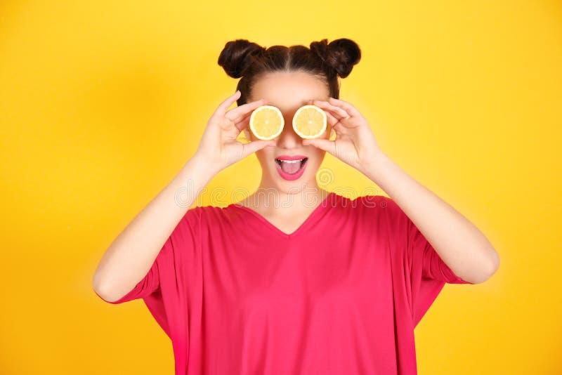 Schöne junge Frau mit Zitrone halbiert nahe Augen stockfotografie