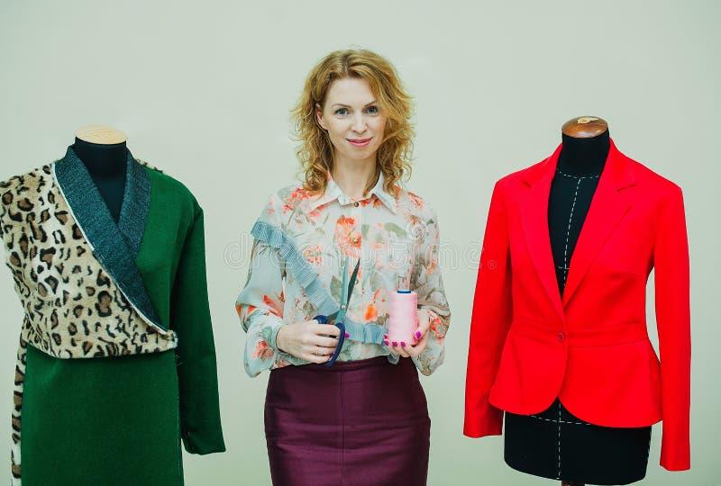 Schöne junge Frau näht Designermantel Leoparddruckmantel und -GRÜN stockbilder