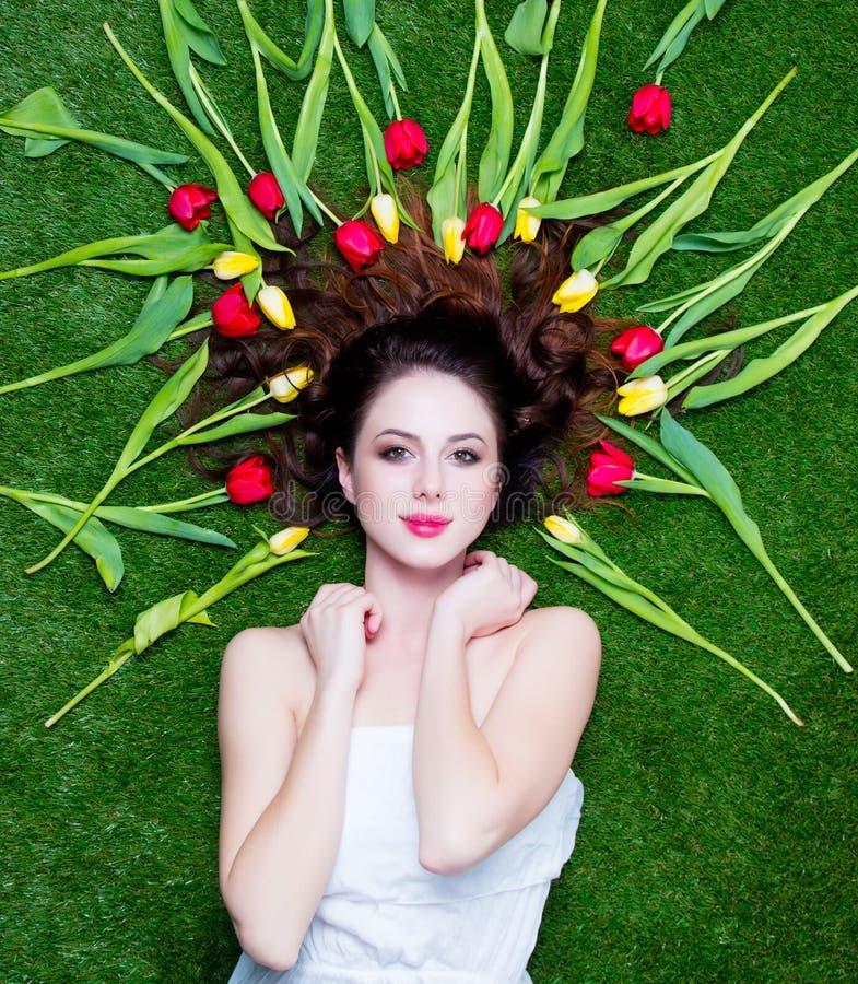 Schöne junge Frau nahe den gelben und roten Tulpen, die auf dem w liegen stockfoto