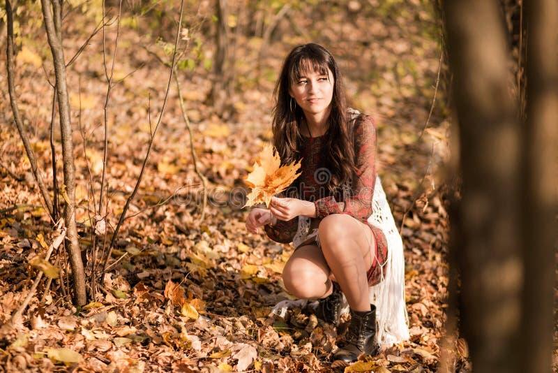 Schöne junge Frau sammelt einen Blumenstrauß von Blättern im Herbstwald lizenzfreie stockfotografie