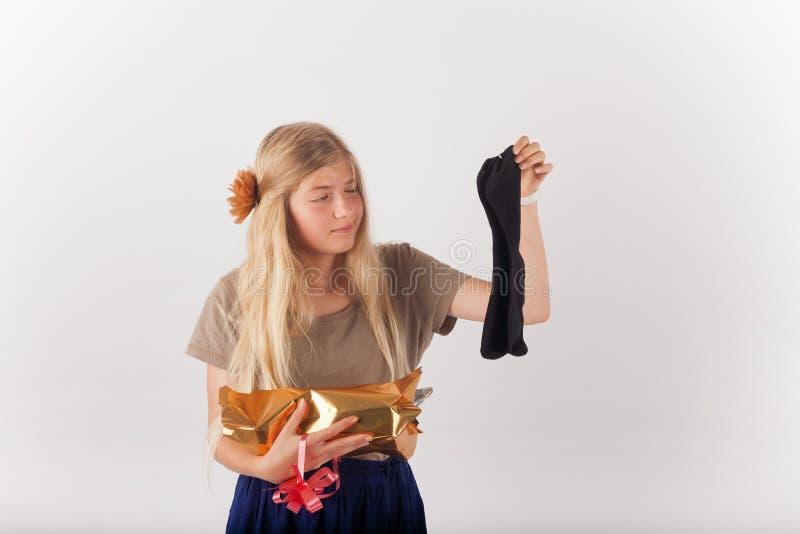 Schöne junge Frau sehr enttäuscht mit ihrem Geschenk lizenzfreies stockfoto