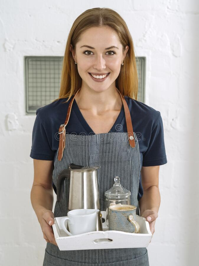 Schöne junge Frau serviert Kaffee lizenzfreie stockbilder