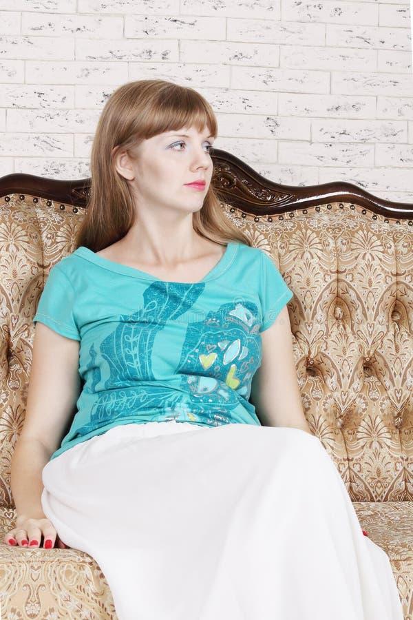 Schöne junge Frau sitzt auf Couch lizenzfreies stockbild