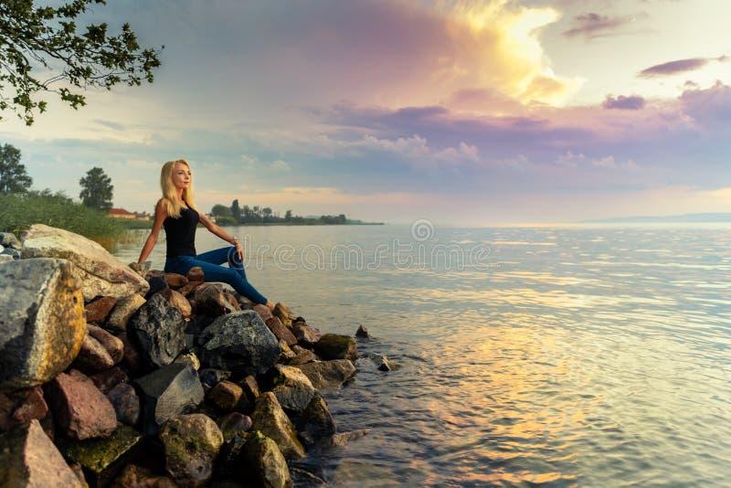 Schöne junge Frau sitzt auf den Felsen durch den Balaton See stockbilder