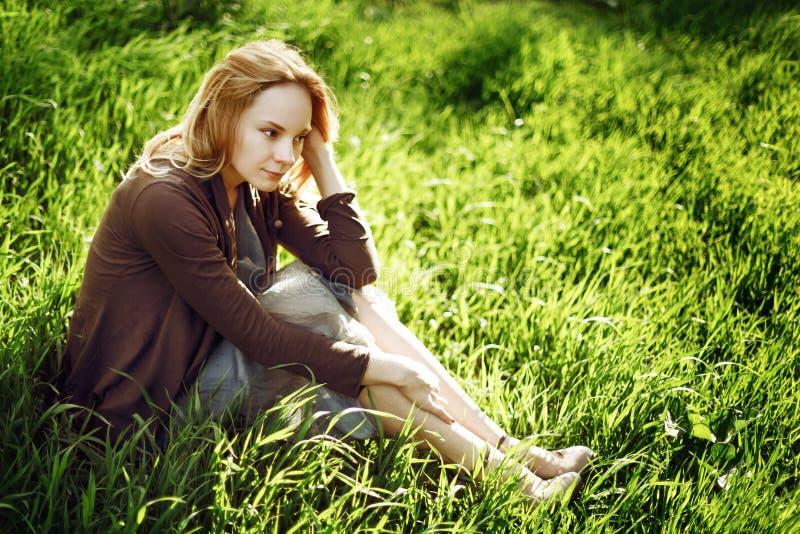 Schöne junge Frau sitzt im Gras. Rel lizenzfreie stockfotografie