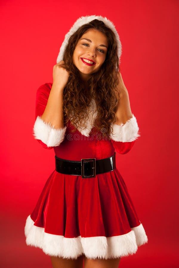 Schöne junge Frau in snata Kleid über rotem Hintergrund stockbild