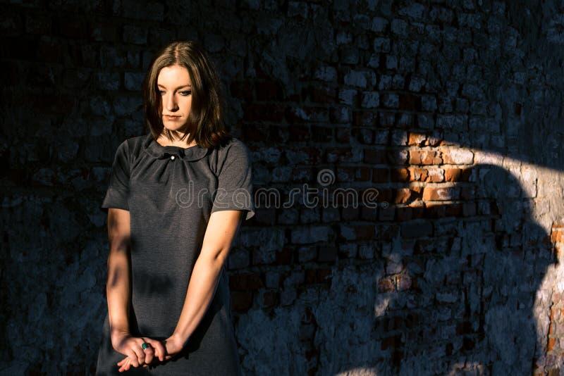 Schöne junge Frau steht nahe der alten Backsteinmauer stockbild