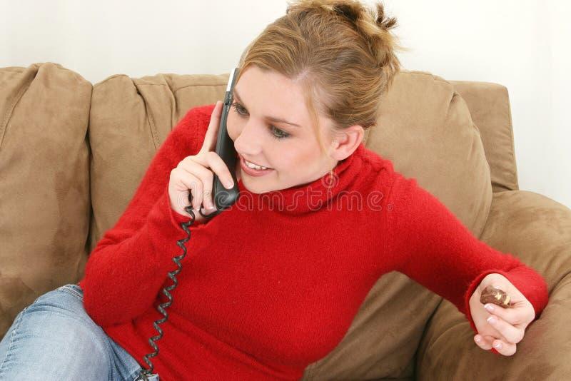 Schöne junge Frau am Telefon Schokoladen essend stockfotos