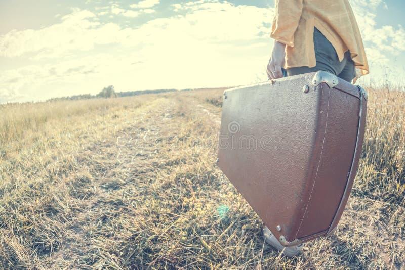 Schöne junge Frau trägt braunen Weinlesekoffer im Feldweg während des Sommersonnenuntergangs Getontes Bild und Reisekonzept lizenzfreie stockbilder