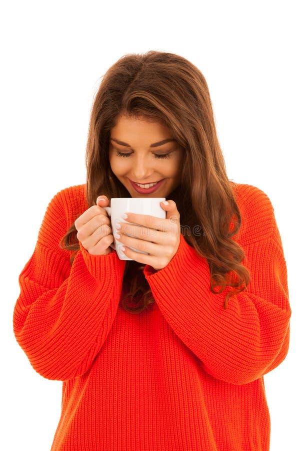 Schöne junge Frau trinkt den Kaffee, der über weißem backgrou lokalisiert wird lizenzfreie stockfotografie