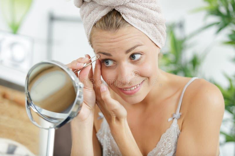 Schöne junge Frau tut Augenbrauenkorrektur stockfoto