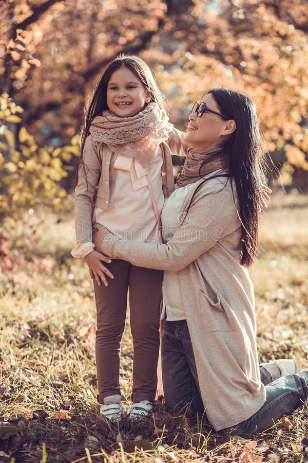 Schöne junge Frau und ihr Kind im Herbst arbeiten im Garten stockbild
