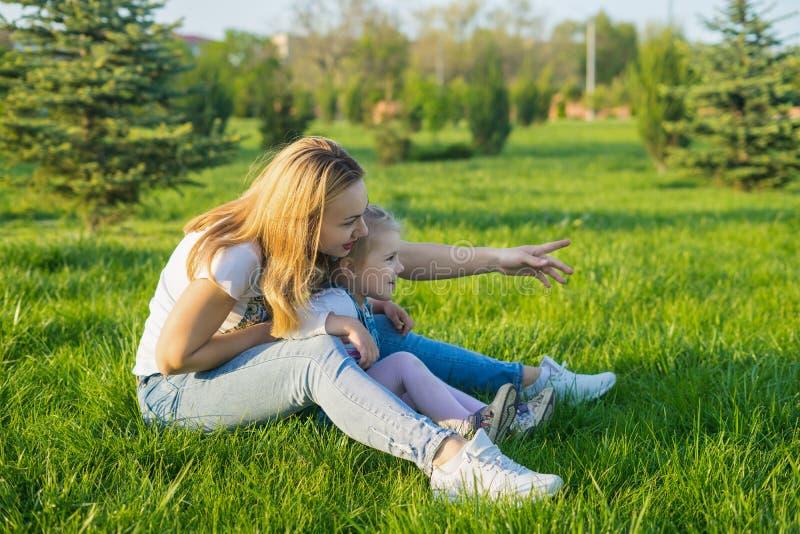 Schöne junge Frau und ihr kleines Tochtersitzen stockbilder