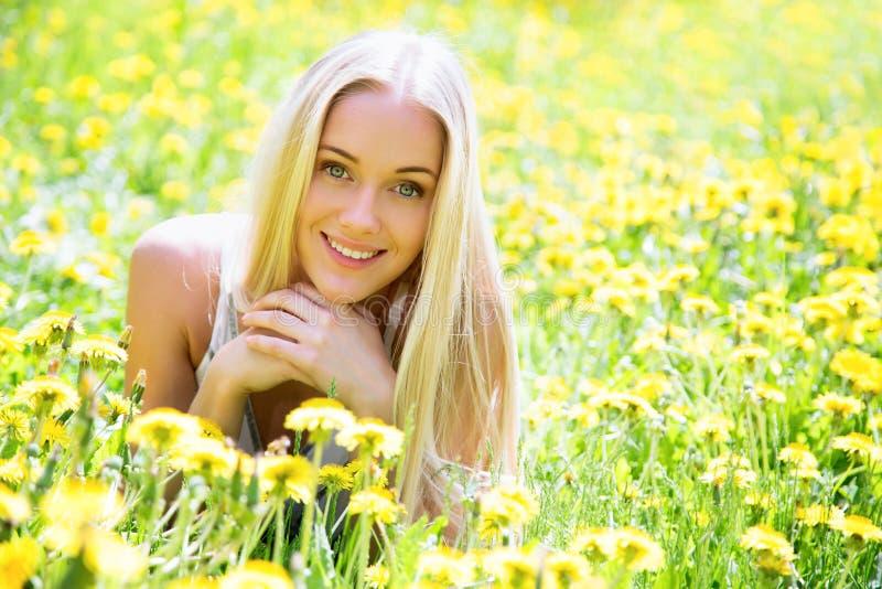 Schöne junge Frau unter den Blumen stockbild