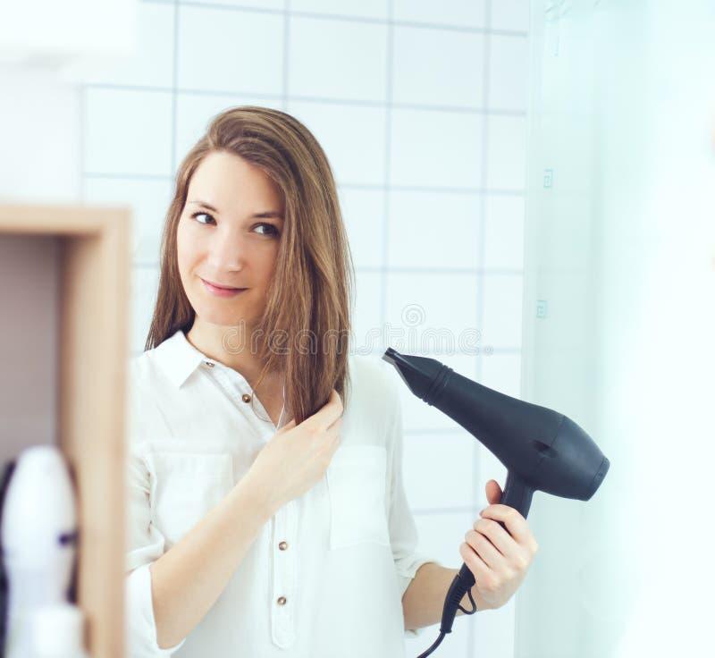 Schöne junge Frau unter Verwendung des Haartrockner-Trocknerhaares Junges asiatisches Mädchen, das Haar mit dem Finger getrennt a stockbilder