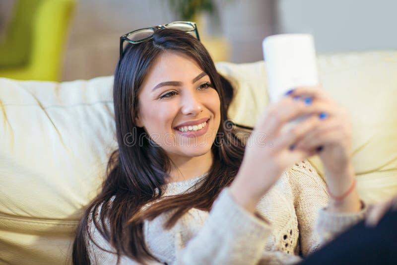Schöne junge Frau unter Verwendung des Mobiltelefons und des Ablesens von guten Nachrichten lizenzfreie stockbilder