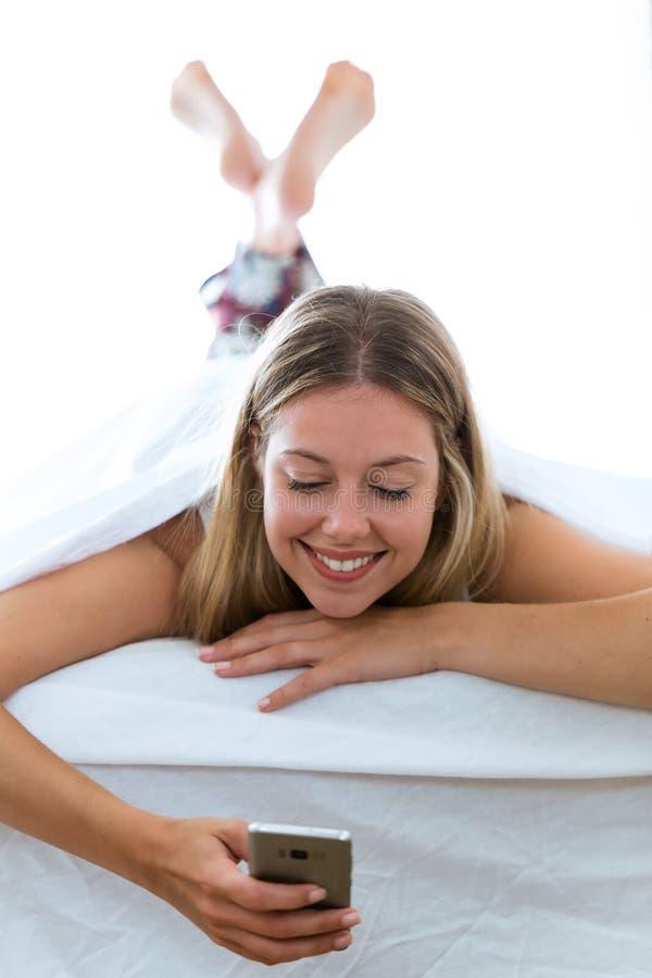 Schöne junge Frau unter Verwendung ihres Handys beim Stillstehen auf dem Bett auf lokalisiertem weißem Hintergrund stockfotos