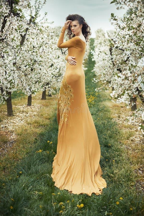 Schöne junge Frau unter wohlriechenden Apfelbäumen lizenzfreies stockfoto
