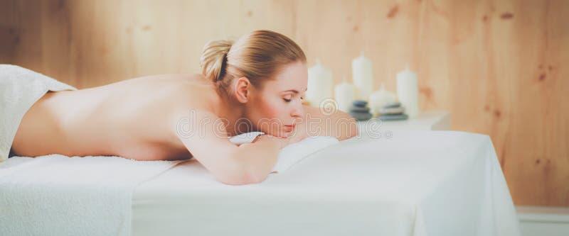 Schöne junge Frau, welche die Badekurortmassage, liegend auf Salon erhält lizenzfreie stockfotos