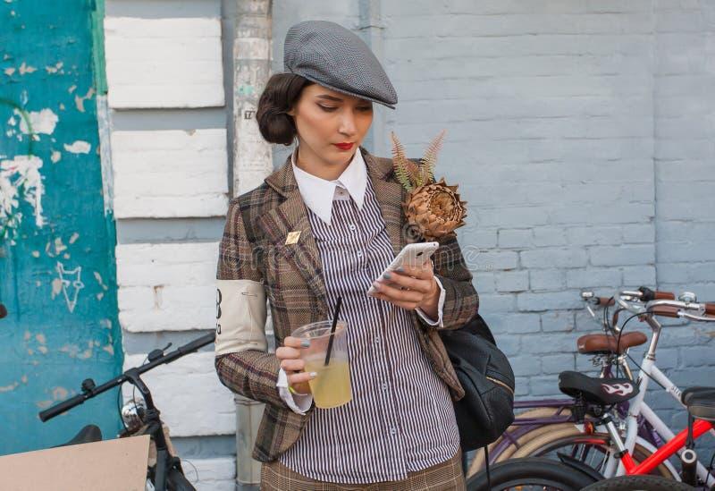 Schöne junge Frauen in der Weinlesekleidung mit dem Handy und Retro- Fahrrad bereit zum Radfahren stockfoto
