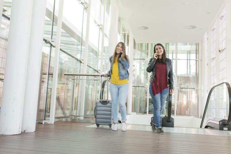 Schöne junge Frauen, die auf ihrem Handy und Lächeln sprechen Reisekonzept am Flughafen, geht sie oben Treppe mit a lizenzfreie stockfotos