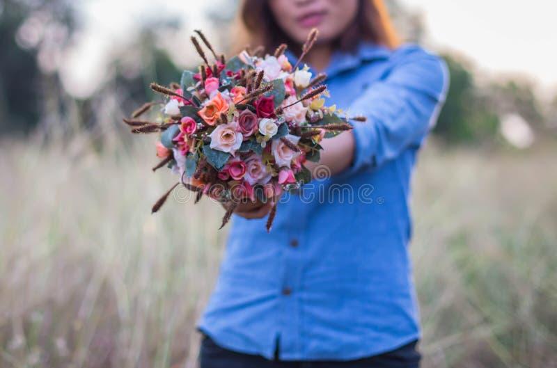 Schöne junge Frauen, die eine Blume auf einem Gebiet halten stockfotos