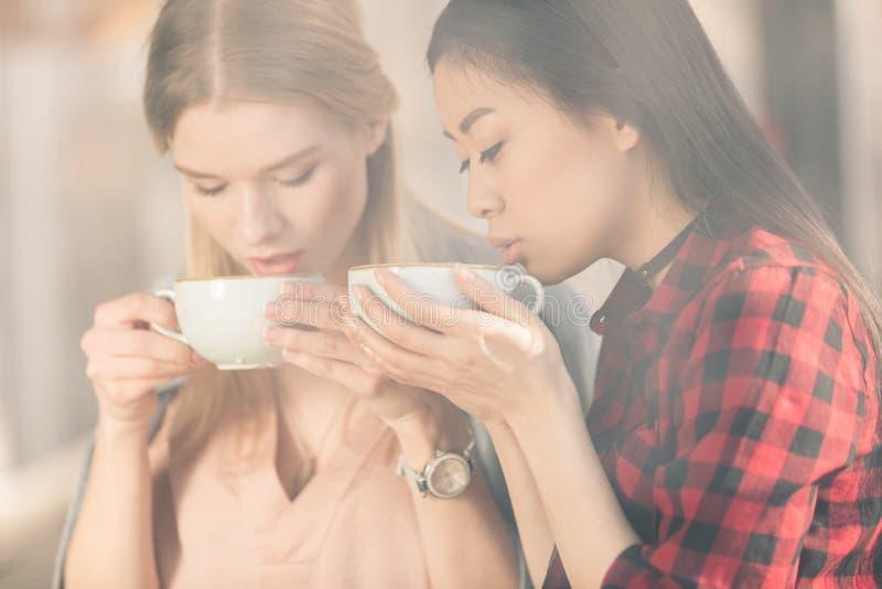 Schöne junge Frauen, die weiße Schalen halten und frischen Kaffeekaffee trinken stockfotografie