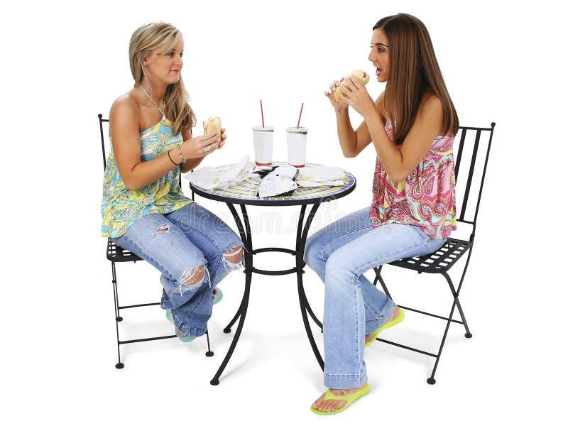 Schöne junge Frauen, die zusammen zu Mittag essen lizenzfreies stockbild