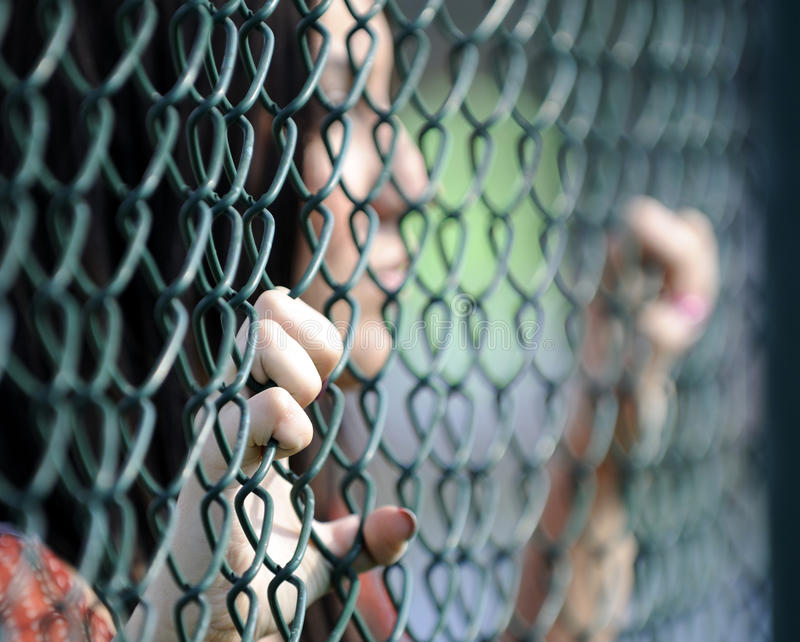 Schöne junge Frauen gegen Zaun stockfotos