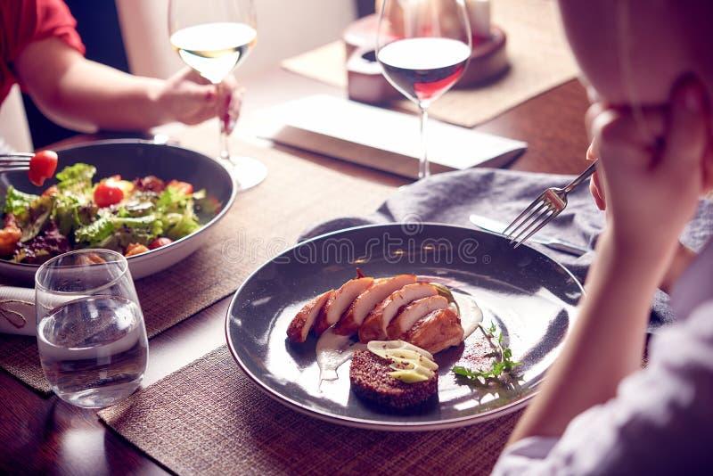 Schöne junge Frauen mit Gläsern Rot und Weißwein im Luxusrestaurant Abendessen oder Mittagessen Essen von Salaten und von Fleisch stockfotos