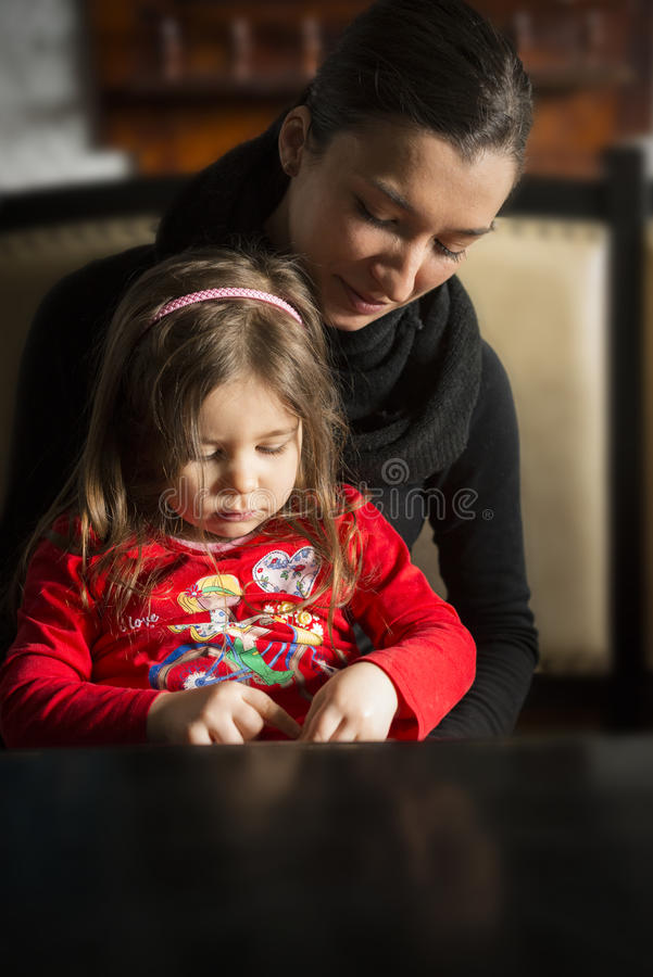 Schöne junge Frauen mit recht kleinem Mädchen in ihren Armen lizenzfreie stockfotografie