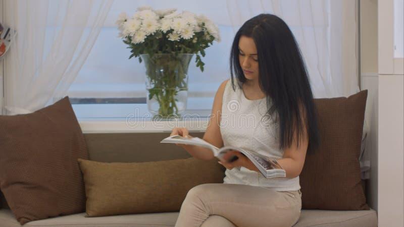 Schöne junge Geschäftsfrau, die auf einem Sofa im Büro mit einer Zeitschrift in ihrer Hand sitzt stockbilder