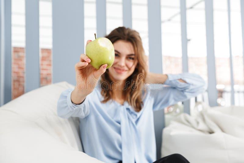 Schöne junge Geschäftsfrau, die auf einer Couch sitzt lizenzfreie stockfotos