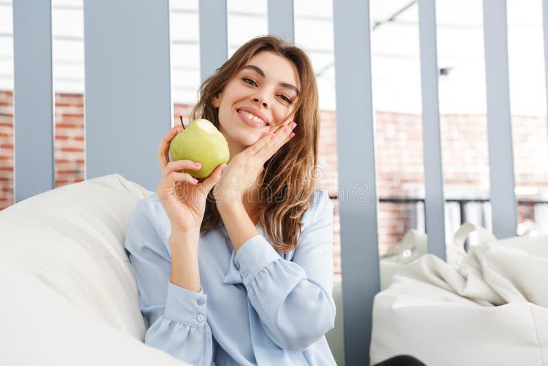 Schöne junge Geschäftsfrau, die auf einer Couch sitzt lizenzfreie stockbilder