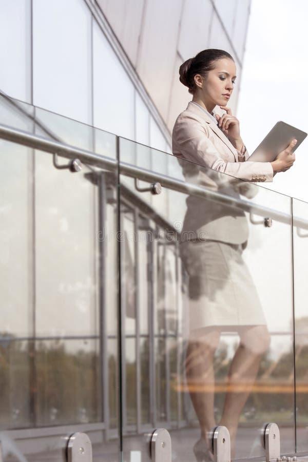 Schöne junge Geschäftsfrau, die digitale Tablette am Bürogeländer verwendet stockfotos