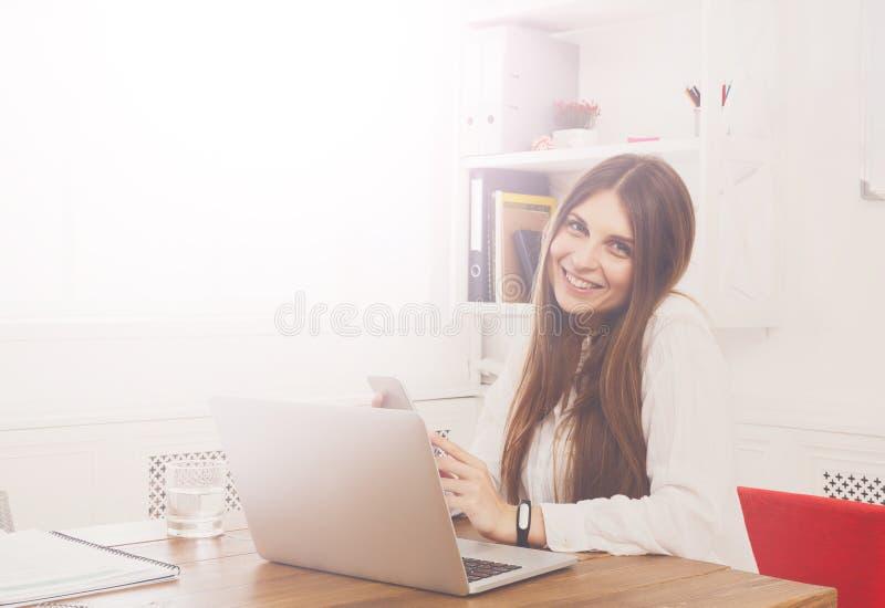 Schöne junge Geschäftsfrau, die durch Schreibtisch mit Laptop sitzt lizenzfreies stockbild