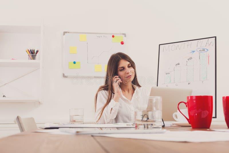 Schöne junge Geschäftsfrau, die einen Anruf durch Handy macht lizenzfreie stockbilder