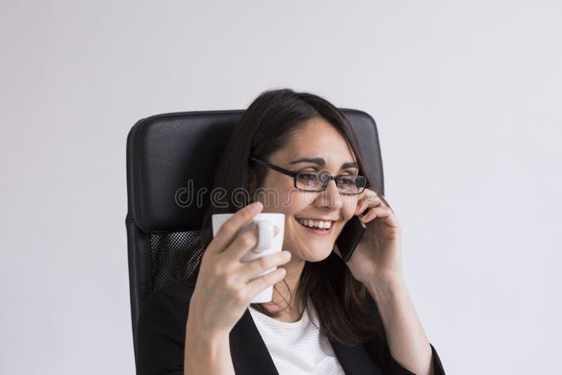 schöne junge Geschäftsfrau, die an ihrem Handy im Büro spricht und einen Tasse Kaffee hält Die goldene Taste oder Erreichen für d lizenzfreie stockfotos