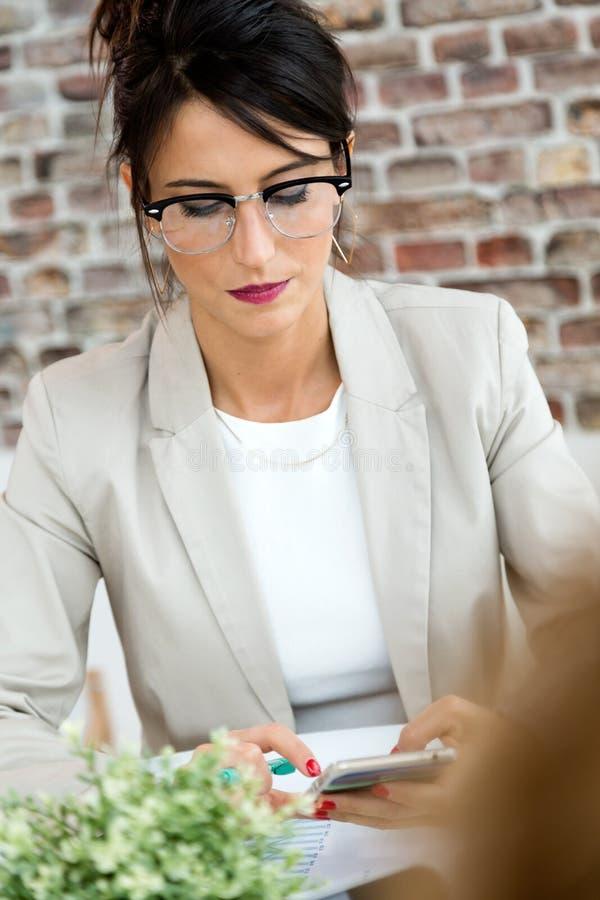 Schöne junge Geschäftsfrau, die ihren Handy im Büro verwendet stockfotografie