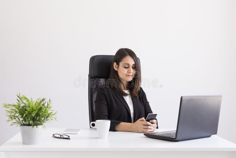 schöne junge Geschäftsfrau, die im Büro, unter Verwendung ihres Laptops und Handys arbeitet Die goldene Taste oder Erreichen für  stockfotos