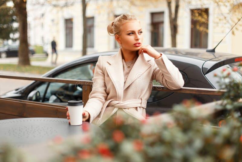 Schöne junge Geschäftsfrau in einem klassischen Mantel stockbild
