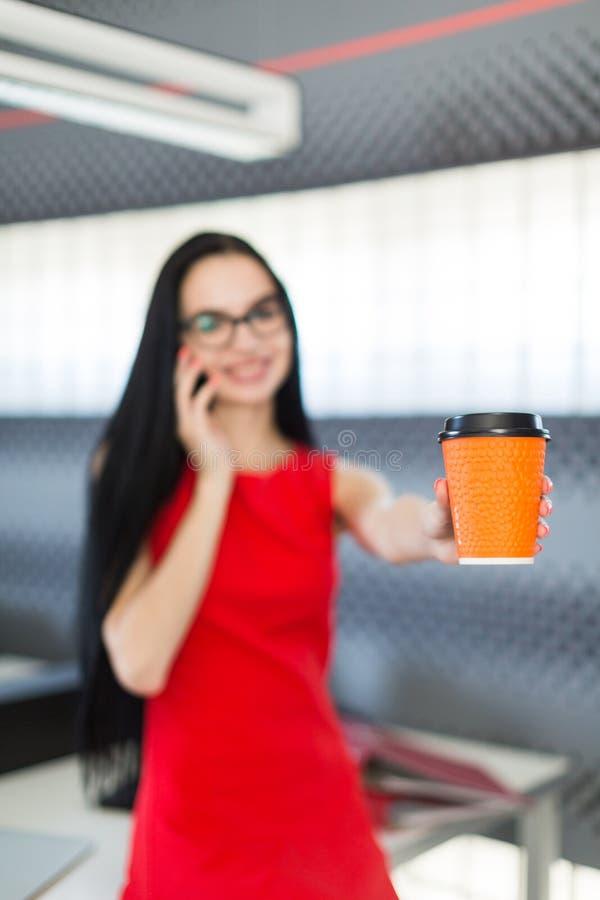 Schöne junge Geschäftsfrau im roten Kleid und Gläser sitzen auf Tabelle in der Büro und Griff coffe Schale stockfotografie