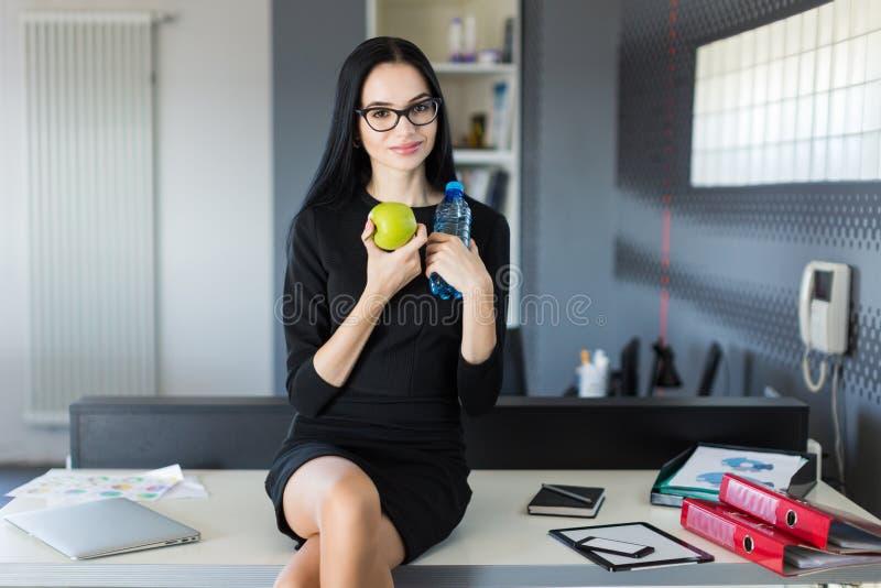 Schöne junge Geschäftsfrau im schwarzen Kleid und Gläser sitzen auf Tabelle im Büro und halten grünen Apfel und Flasche stockbild