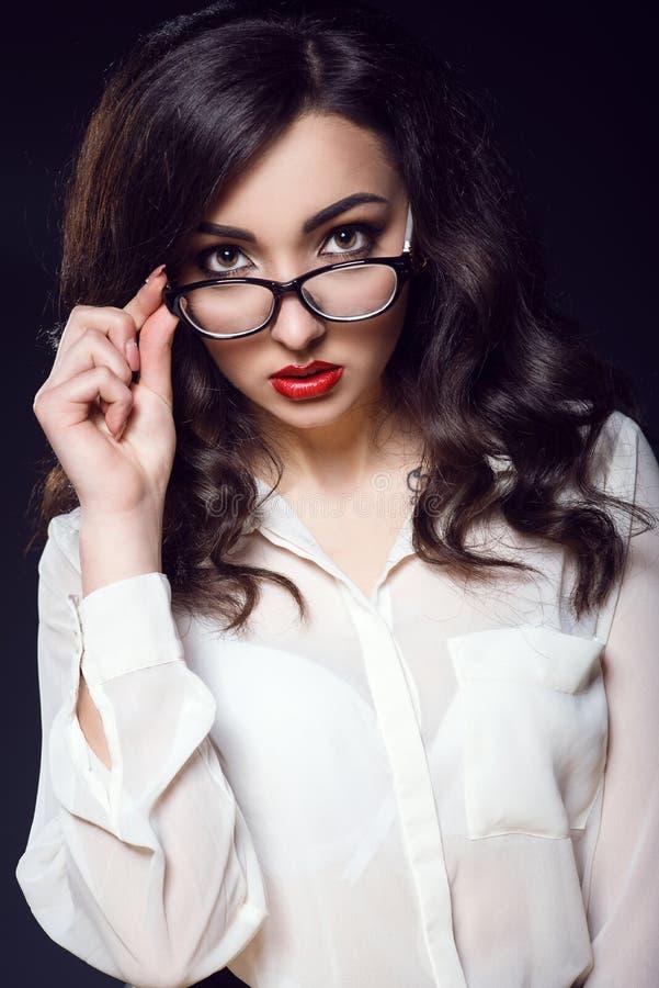 Schöne junge Geschäftsfrau mit dem dunklen gewellten Haar und roten den Lippen, welche die weiße Seidenbluse gerade schaut über i stockfotos