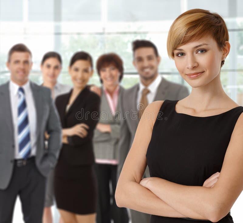 Schöne junge Geschäftsfrau und Geschäftsteam stockfotografie