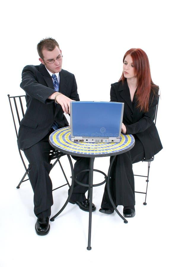 Schöne junge Geschäftsfrau und Mann am Tisch mit Laptop stockbild