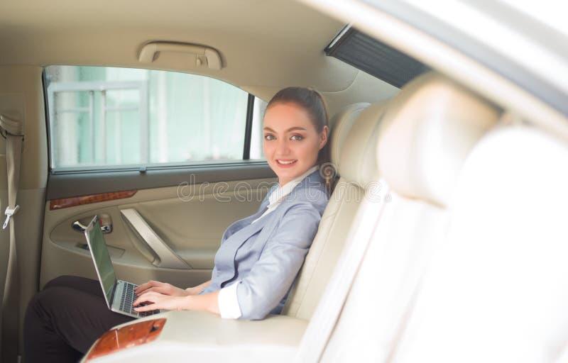 Schöne junge Geschäftsfrau unter Verwendung des Laptops und des lächelnden Weilesi stockfoto