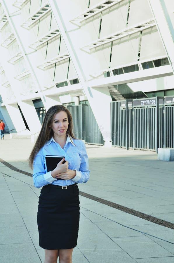 Schöne junge Geschäftsfraustellung und Halten eines Notizbuches, einen schwarzen Rock und Schuhe tragend und untersuchen den Abst lizenzfreies stockbild