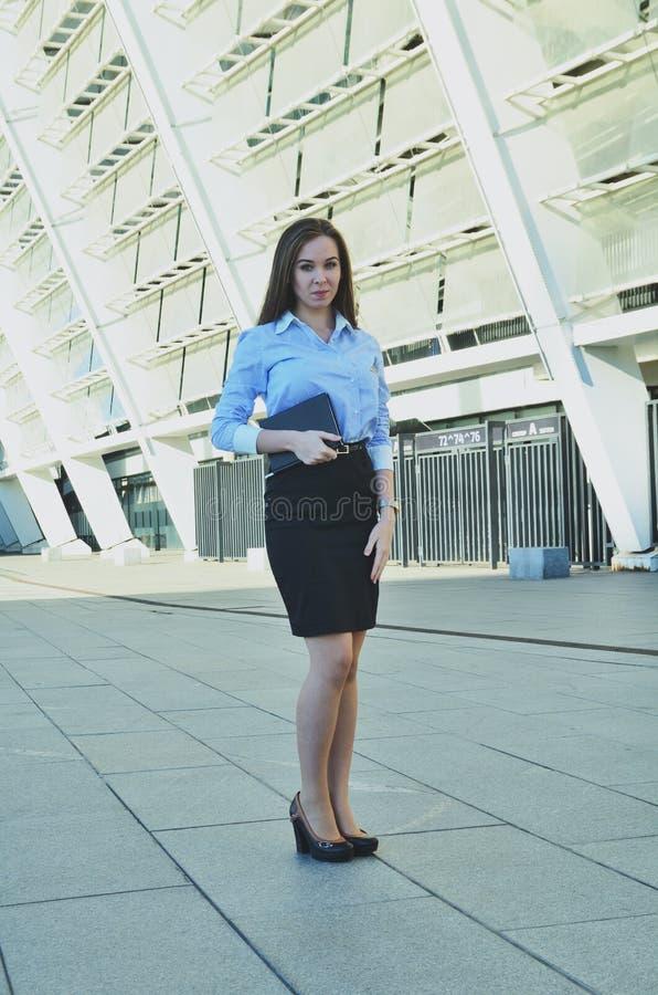 Schöne junge Geschäftsfraustellung und Halten eines Notizbuches, einen schwarzen Rock und Schuhe tragend und untersuchen den Abst lizenzfreie stockfotos