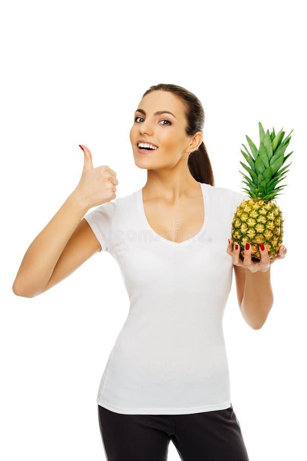Schöne junge glückliche brunette Frau im weißen T-Shirt hält Ananas Stände, die das Lächeln auf weißem Hintergrund aufwerfen stockfoto